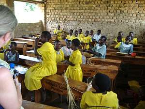 School children, many of them in bright yellow uniforms, in their classroom at Champona school