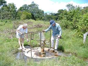 Two members of Abingdon Vesper Rotary club inspect the village well in Mubende