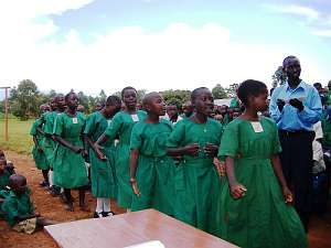 A group of schoolchildren, all dressed in green uniforms, taking part in a welcoming celebration at Mugungulu school