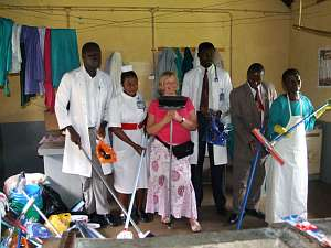 A group of hospital staff show off their new mops, buckets, brushes and brooms