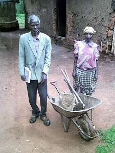A man and woman stand next to a wheel barrow containing assorted farming implements