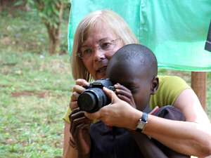 A Rotary member holds her camera so that a young child from Thika can look through  the lens