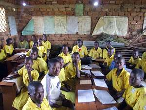 School children, many of them in bright yellow uniforms, sitting at their desks